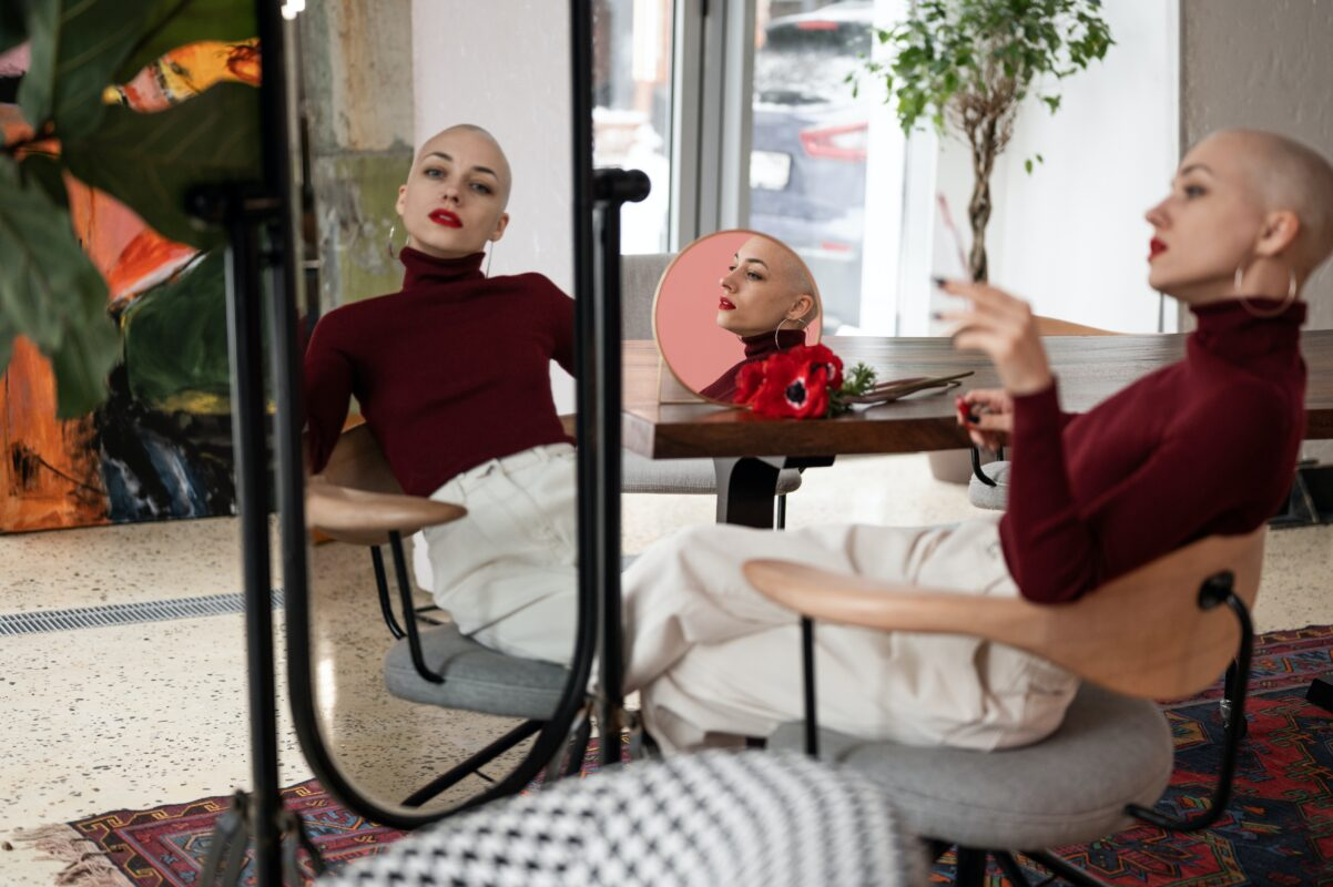 a photo of a bald lady looking at a mirror for a blog on 6 practical tips to find your personal style